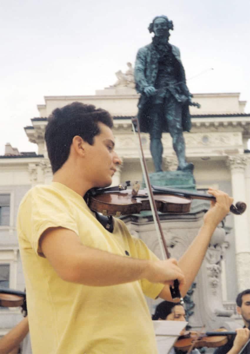 José Manuel Gil de Gálvez, autor del artículo, tocando ante la estatua de Giuseppe Tartini en la Plaza Tartini de Pirano (Eslovenia, 2000)